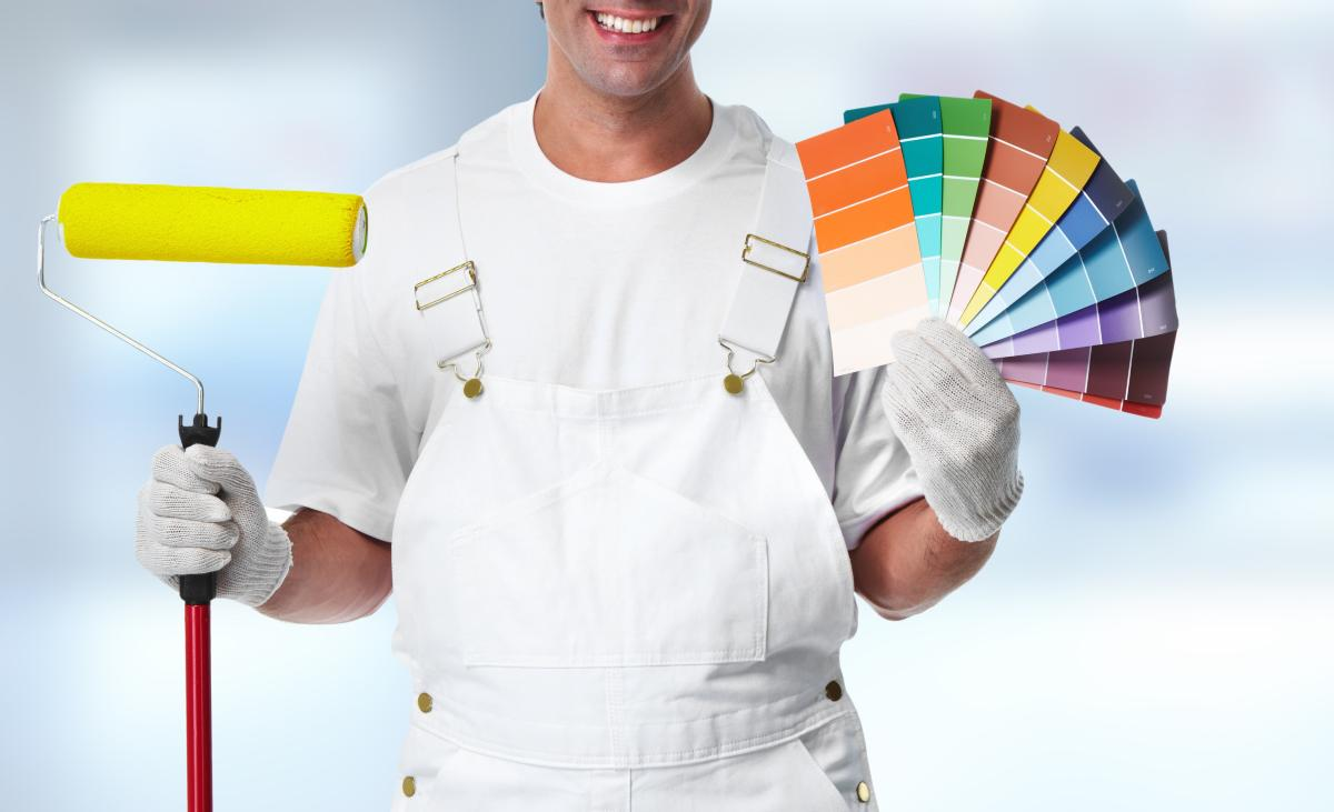 Professional painter holding a roller and a range of colour cards